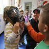 Essex: Kenneth Pyburn tries on the mask of his father, Manchester Firefighter Dennis Pyburn, during a fire safety demonstration at Lil' Sprouts of Essex yesterday morning as part of Fire Safety week. Photo by Kate Glass/Gloucester Daily Times