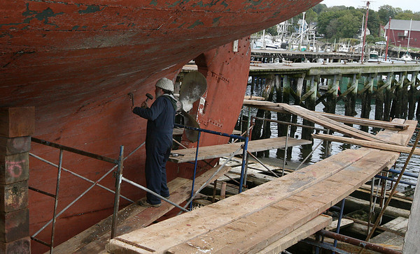 Gloucester: David Short scrapes caulking away from a plank that needs to be replaced on the schooner Roseway while it is drydocked at Gloucester Marine Railways. Photo by Kate Glass/Gloucester Daily Times