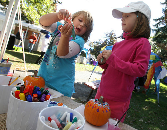 Rockport: Emily Hale shows Abby Marshall the color she wants to use to decorate her pumpkin at the Rockport Harvest Festival on Saturday afternoon. Photo by Kate Glass/Gloucester Daily Times