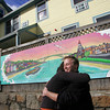Gloucester: Gloucester senior Cole Herbst hugs Liz Moran, the director of Compass where Herbst attends school, at the unveiling of the mural he painted outside the Action Shelter on Main Street Friday afternoon.  Herbst has been working on the mural since January and iart work is now part of the beautification and renovations of the shelter which now includes four bran new living quarters. Mary Muckenhoupt/Gloucester Daily Times