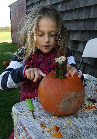 Essex: Alice Schwechheiner carves a pumpkin during the Cogswell's Grant Pumpkin Festival. Photo by Kate Glass/Gloucester Daily Times