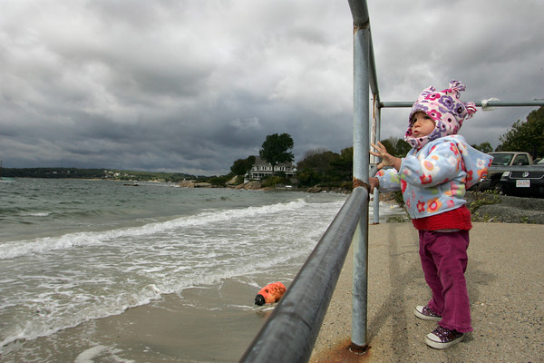 Gloucester: Juno Kullgren, 16 months, watches the high tide crash onto Niles Beach Thursday morning.  Big waves and high tide brought the water right up to the wall. Mary Muckenhoupt/Gloucester Daily Times