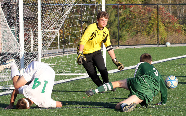 A fumble between Manchester Essex Regional High School defender Alex Walder, left, and North Reading High School forward Dylan Poor ended in a save by Manchester Essex goalkeeper Chris Xavier. Jesse Poole/Gloucester Daily Times