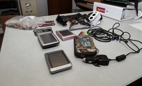 A bunch of stolen goods that were recovered include car GPS units, sunglasses, a bag of change, cigar cutters, a phone charger and wallet.  David Le/Gloucester Daily Times