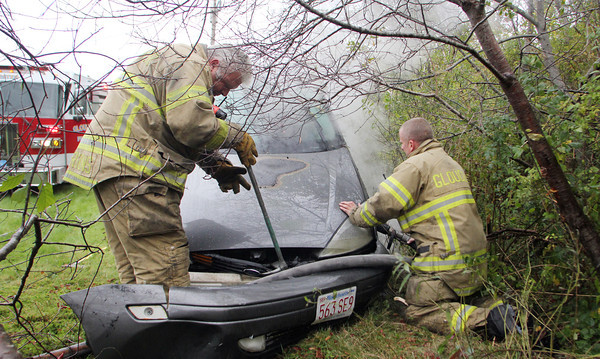 Gloucester firefighters Robbin Parsons, left, and Mike Smith work to cool down the flaming engine of a Ford Focus after it rammed into a wooded area off Exit 12 near Nichols Candies in Gloucester on Wednesday afternoon, after the driver's accelerator stuck. Jesse Poole/Gloucester Daily Times Oct. 26, 2011