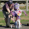 Vicki Halmen, of Georgetown, helps her daughter Julia, 3, peddle her bike while they were visiting family in Rockport over the long weekend. David Le/Gloucester Daily Times
