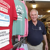 Joe Ciolino, owner of The Weathervane Gift Shop on Main St. in downtown Gloucester hangs a sign welcoming visitors from The Seven Seas Navigator cruiseship on a t-shirt on the door to his shop. David Le/Gloucester Daily Times