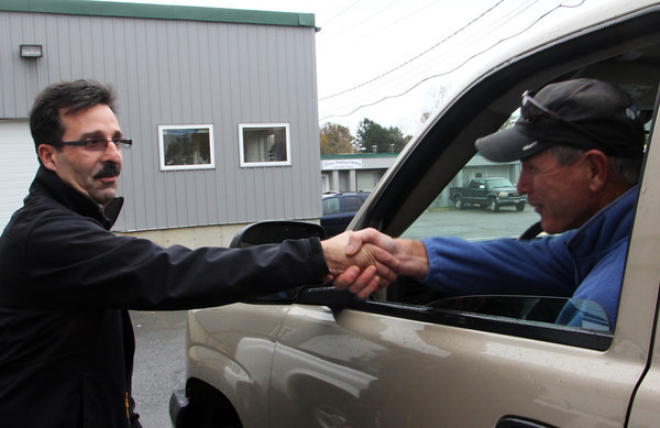 Steve Curcuru, left, incumbent Ward 3 councilor, shakes the hand of Donald Riley, a Ward 3 lobsterman, as he drives by Curcuru on his re-election campaign. Jesse Poole/Gloucester Daily Times Oct. 26, 2011