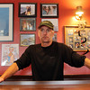 Gregg Sousa, owner of the Crow's Nest, stands in front of photos of the Andrea Gail and its crew 20 years after what's now refered to as the Perfect Storm. Jesse Poole/Gloucester Daily Times Oct. 27, 2011