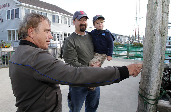 Captain Paul Frontiero of 7 Seas Whale Watch, left, shows Adam Rosell and his son Aidan, 4, of Gloucester, a jawbone from a fin whale that he displays proudly outside his building. 7 Seas will be making its last trip of the season this Sunday.  David Le/Gloucester Daily Times