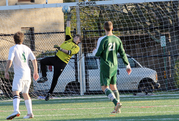 Manchester Essex Regional High School goalkeeper Chris Xavier, reaches and saves a shot by North Reading High School midfielder Tyler Stanieich, right, Tuesday late afternoon. Jesse Poole/Gloucester Daily Times