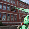 Workers on a lift bucket adjust the windows on the Central Grammar Building on Dale Ave. on Friday afternoon. David Le/Gloucester Daily Times.