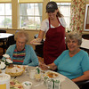 Marianne Watts, left, and Lydia Souza, right, both of Rockport, wait patiently as Michelle Cook, a Site Manager for Senior Care delivers dessert at the Senior Center on Friday morning. David Le/Gloucester Daily Times