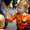 Hailey Powers, 2, of Gloucester, says hello to a friend at the Sawyer Free Library by waving her hand in his face on Thursday morning. Jesse Poole/Gloucester Daily Times Oct. 27, 2011