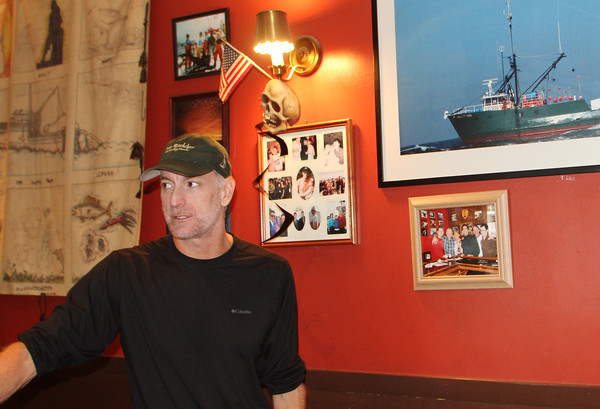 Gregg Sousa, owner of the Crow's Nest, stands next to a photo of the Andrea Gail 20 years after what's now refered to as the Perfect Storm. Jesse Poole/Gloucester Daily Times Oct. 27, 2011
