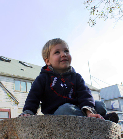 Nicholas Bilenchi, 2, of Rockport enjoys his granite perch on Bearskin Neck Monday morning. Jesse Poole/Gloucester Daily Times