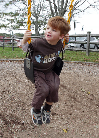 Connor Dickson, 3, of Manchester, swings on the set at Masconomo Park on a warm October day. David Le/Gloucester Daily Times