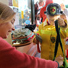 Beckett Guarino, 4, dressed as a fireman, accepts some Halloween treats from Bethany Carlson, owner of the John Tarr Store in Rockport, as the rest of Sandy Bay Preschool waits behind him in anticipation of candy. Jesse Poole/Gloucester Daily Times Oct. 31, 2011