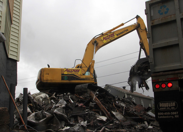 An Action Emergancy Services excavator works to clean up the debris left by the Mansfield Street fire in mid-September. Jesse Poole/Gloucester Daily Times Oct. 27, 2011