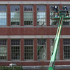 Workers paint the window frames on the front of the Central Grammar Apartment Building on Dale Ave. David Le/Gloucester Daily Times.