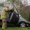 Gloucester firefighters Robbin Parsons, left, and Mike Smith help Tally's Towing pull a Ford Focus out of the woods off Exit 12 near Nichols Candies in Gloucester on Wednesday afternoon, after the driver's accelerator stuck. Jesse Poole/Gloucester Daily Times Oct. 26, 2011