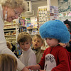 Thing 1, Henry Chadbourne, 4, asks Carol Tuck, owner of Tuck's Candy and Gifts, for enough Halloween treats for Thing 2, his little sister Cecilia, 2, as other Sandy Bay Preschool children look on, waiting for their share of the goods. Jesse Poole/Gloucester Daily Times Oct. 31, 2011