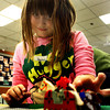 Sarah-Jean Collins, 7, of Gloucester, creates a bardyard out of Legos, placing the horses in just the right place, she says. Jesse Poole/Gloucester Daily Times