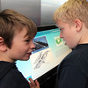 Allegra Boverman/Gloucester Daily Times. Veterans' Memorial Elementary School fourth graders Mark Lane and Tyler Bryan try to listen to the sounds of whales while using an interactive kiosk during a  visit to  Maritime Gloucester with their classmates on Wednesday morning.