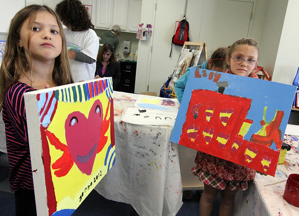 """Allegra Boverman/Gloucester Daily Times. From left: Jenna Church, 7, and Lily King, 7, who are in the Pathways for Children Art Club, show their finished paintings that will be available for auction at the Pathways """"A Place at the Table"""" gala on Nov. 9."""