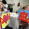 "Allegra Boverman/Gloucester Daily Times. From left: Jenna Church, 7, and Lily King, 7, who are in the Pathways for Children Art Club, show their finished paintings that will be available for auction at the Pathways ""A Place at the Table"" gala on Nov. 9."