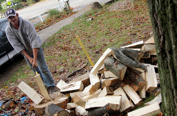 Allegra Boverman/Gloucester Daily Times. Steve Jermyn of Essex Avenue in Gloucester was splitting wood from an elm tree that was part of a group of a few trees that were cut down at the home of his mother-in-law in Essex just before the hurricane struck the area so that they wouldn't fall on the neighbors' home. Now he is splitting the wood to season it for later use this coming winter.