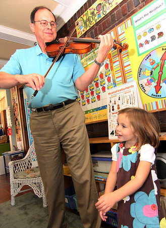 """Allegra Boverman/Gloucester Daily Times. Don Goldenbaum, grandfather of Ruby McElhenny, a student in the Pre-Kindergarden/Kindergarten at Eastern Point Day School, was visiting the school on Thursday morning to talk about being a musician. He is a longtime violinist who performs semi-professionally with three different orchestraa, and is concertmaster at one of them in his hometown of Kansas City. He talked about the kinds of sounds violins can make - happy, sad, fast, slow, high and low. He improvised pieces based on notes that the children asked him to play, and performed such songs as """"The itsy-bitsy spider,"""" while they sang along. He also took requests, including playing the theme to """"Star Wars,"""" and the theme of its character Darth Vader. He also played """"You are my Sunshine,"""" as Ruby sang, above and with the whole class, """"The Instrument Song,"""" while the class performed on imaginery instruments and marched around the room."""