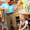 "Allegra Boverman/Gloucester Daily Times. Don Goldenbaum, grandfather of Ruby McElhenny, a student in the Pre-Kindergarden/Kindergarten at Eastern Point Day School, was visiting the school on Thursday morning to talk about being a musician. He is a longtime violinist who performs semi-professionally with three different orchestraa, and is concertmaster at one of them in his hometown of Kansas City. He talked about the kinds of sounds violins can make - happy, sad, fast, slow, high and low. He improvised pieces based on notes that the children asked him to play, and performed such songs as ""The itsy-bitsy spider,"" while they sang along. He also took requests, including playing the theme to ""Star Wars,"" and the theme of its character Darth Vader. He also played ""You are my Sunshine,"" as Ruby sang, above and with the whole class, ""The Instrument Song,"" while the class performed on imaginery instruments and marched around the room."
