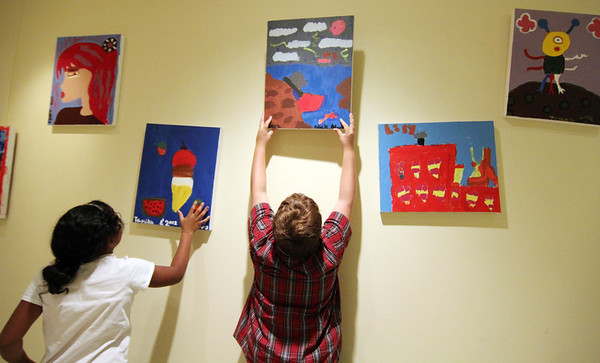 """Allegra Boverman/Gloucester Daily Times. From left: Tamika Gonzalez, 10, and Nick Nunes, 10, hang their finished paintings up on a wall at Pathways for Children where members of the Art Club have placed their works until they go up for auction at the upcoming """"A Place at the Table"""" gala on Nov. 9."""