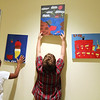 "Allegra Boverman/Gloucester Daily Times. From left: Tamika Gonzalez, 10, and Nick Nunes, 10, hang their finished paintings up on a wall at Pathways for Children where members of the Art Club have placed their works until they go up for auction at the upcoming ""A Place at the Table"" gala on Nov. 9."