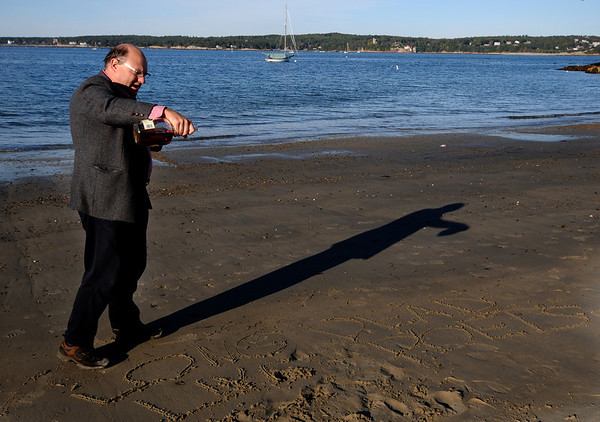"""JIm Vaiknoras/Gloucester Times: Walter Skold pour  adrink from a bottle of cognac over the words"""" Long Live Dead Poets"""" scratched in the sand in memory of local poet Vincent Ferrini on Niles Beach in Gloucester early Monday morning as part of Dead Poets Remembrance Day."""