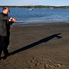"JIm Vaiknoras/Gloucester Times: Walter Skold pour  adrink from a bottle of cognac over the words"" Long Live Dead Poets"" scratched in the sand in memory of local poet Vincent Ferrini on Niles Beach in Gloucester early Monday morning as part of Dead Poets Remembrance Day."