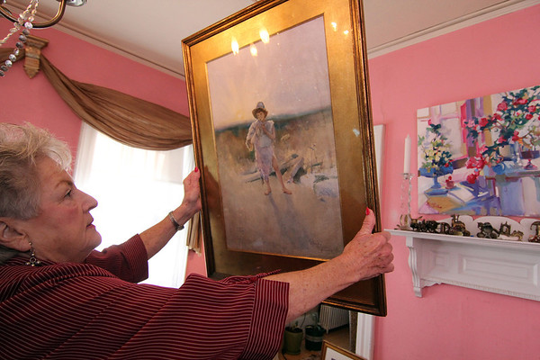 Allegra Boverman/Gloucester Daily Times. Ruth Brown of Rockport talks about the works of art she has been collecting over the years, including the piece by Rhoda Holmes Nichols. A work by Frank Federico is at upper right on her wall.