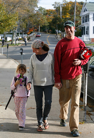 Allegra Boverman/Gloucester Daily Times. Cosima Mosher-Owens, 5, left, of Rockport, was picked up from the bus stop along Mount Pleasant Street in Rockport on Tuesday afternoon by Heather Mosher and Frank Militello, and Cosima's grandparents Donald and Christine Mosher, too. Her grandmother gave her a new talking witch-shaped flashlight for Halloween as she came off the bus.