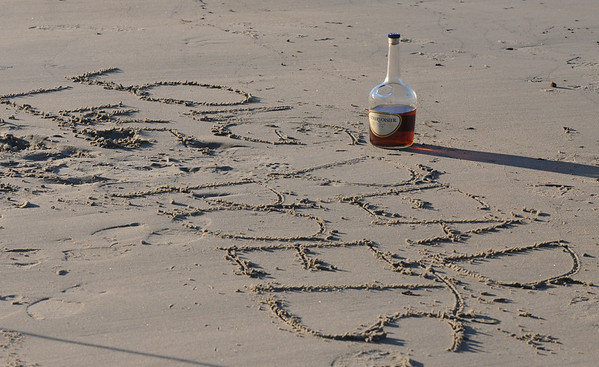"""JIm Vaiknoras/Gloucester Times: A half empty bottle of cognac sit near the words """" Long Live Dead Poets"""" scratched in the sand in memory of local poet Vincent Ferrini on Niles Beach in Gloucester early Monday morning as part of Dead Poets Remembrance Day."""