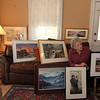 Allegra Boverman/Gloucester Daily Times. Ruth Brown of Rockport talks about the works of art she has been collecting over the years including the works near her. From left on the couch are a work by Ruth Minas, a work by Betty Lou Schlemm; at her feet from left are works by Mary McGlyn, Peter Bodge and on the easel, Frank Federico. On the wall behind are, from left: a work by Florence Bradenberg and Tom Sutherland. At upper left on the wall is a work by Charles Syvertson.