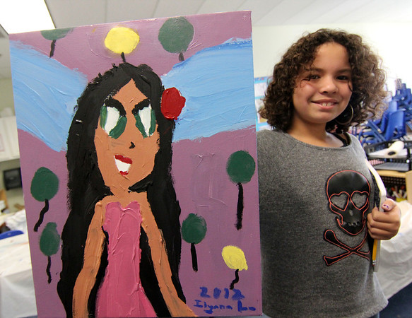 """Allegra Boverman/Gloucester Daily Times. Ilyana Lorenzana, 8, shows off her finished painting that she created as part of the Pathways for Children Art Club. Her painting and that of other kids will be auctioned at the upcoming Pathways """"A Place at the Table"""" gala on Nov. 9."""
