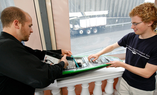Allegra Boverman/Gloucester Daily Times. From left, Olin College Robotic Sailing Team members James Regulinski, a senior, and Eric Schneider, a sophomore, put the controls back into a their radio controlled boat they were showing on Thursday to city, Olin and Endicott College officials.