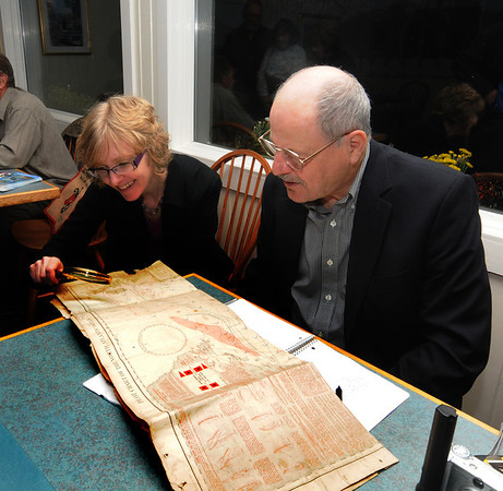 Jim Vaiknoras/Gloucester Daily Times: Lynn Havighurst shows a Pilot Chart to map expert Vincent Caravella at the 4th annual Essex Antiques Appraisal Night At Periwinkles Restaurant. The chart  dating from 1889 shows locations of possible storms and has sailing advice for ships in storms.