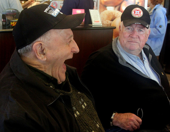 Allegra Boverman/Gloucester Daily Times. From left: Nick Barletta and Steve Crowell talk with some of their friends at Dunkin Donuts about the benefits of having a grocery store in Rockport again.