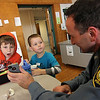 Allegra Boverman/Gloucester Daily Times. Thomas Williams, left, and Alex Wilt, both Essex Elementary School kindergarteners, look at photos that Essex Patrolman Rob Gilardi was showing them from his trip to the Canadian Rockies. They were participating in the annual Mix-It-Up lunch held at the school, during which pupils were seated at tables with children they don't normally sit with, and with a few special visitors.