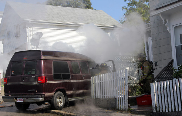 Allegra Boverman/Gloucester Daily Times. Gloucester firefighters work at the scene of a conversion van fire at 13 Millett Street in Gloucester on Friday.