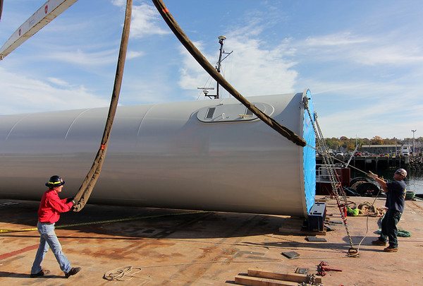 Allegra Boverman/Gloucester Daily Times. Pieces of one wind turbine destined for Gloucester Engineering in the Blackburn Industrial Park arrived by barge on Tuesday to Cruiseport. Three large pieces were unloaded and will be moved on Wednesday, Thursday and Friday. The blades will arrive later on by truck from Pennsylvania. Working to prepare the base to be moved from barge to the Cruiseport parking lot are Jeff Berry, left, and ironworker Jason Jenkins, of Local 6.