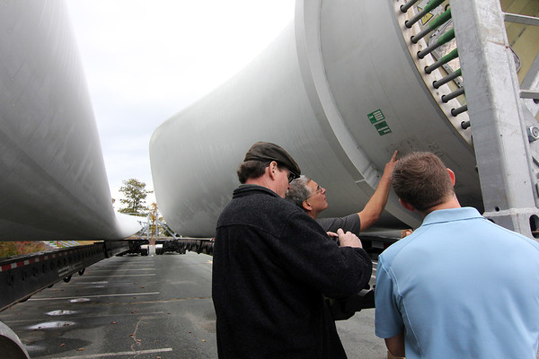 Allegra Boverman/Gloucester Daily Times. Varian division of Applied Materials employees have been keeping a close eye on the wind turbine pieces as they arrive and are being placed for installation at their facility in the Blackburn Industrial Park. Varian coworkers from left: Ed MacIntosh of Amesbury, Dave Chipman of Lynn, and Mike Schrameyer of Beverly examine the blades closely on Friday.
