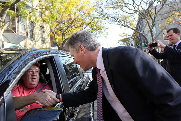 "ALLEGRA BOVERMAN/Gloucester Daily Times. Republican U.S. Sen. Scott Brown, right, runs into the middle of Main Street in Gloucester on Friday to talk with Buddy Hackett of Gloucester as he drove by. Scott was downtown ""walking and talking"" with voters and visited many businesses along the way."